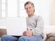 Germany, Hamburg, Senior man using laptop, portrait (thumbnail)