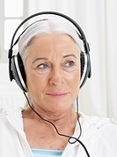 Germany, Hamburg, Senior woman listening music
