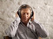 Germany, Hamburg, Senior man listening music with eyes closed