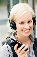 Germany, Bavaria, Munich, Young woman listening music, smiling, portrait
