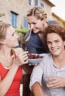Italy, Tuscany, Magliano, Young man and women with bowl of cherries, smiling