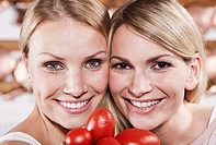 Italy, Tuscany, Magliano, Close up of two young women holding tomatoes in kitchen, smiling, portrait