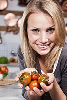 Italy, Tuscany, Magliano, Close up of young woman holding tomatoes in kitchen, smiling, portrait