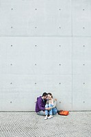 Germany, Berlin, Couple sitting in front of large wall on sidewalk