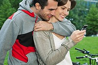 Germany, Berlin, Couple using cell phone in park