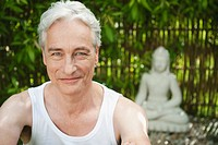 Germany, Bavaria, Mature man smiling with buddha statue in background