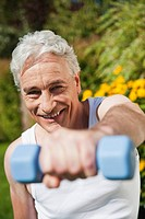 Germany, Bavaria, Mature man doing exercise with dumbbells (thumbnail)