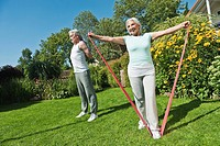 Germany, Bavaria, Man and woman exercising in garden, smiling