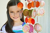 Germany, Bavaria, Girl with decorative sea shells wind chime, smiling, portrait