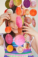 Germany, Bavaria, Girl looking through decorative sea shells wind chime