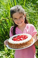 Germany, Bavaria, Girl holding cake, smiling, portrait