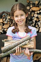 Germany, Bavaria, Girl holding firewood, smiling, portrait