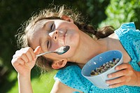 Germany, Bavaria, Girl eating cereal food, smiling, portrait
