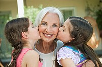 Germany, Bavaria, Granddaughters kissing grandmother, close up