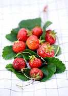 Fresh strawberries and leaves on a tea towel
