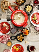 Swiss cheese fondue with potatoes, bread and vegetables seen from above