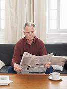 Germany, Hamburg, Senior man reading newspaper