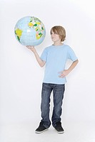 Germany, Bavaria, Ebenhausen, Boy holding earth globe against white background, smiling