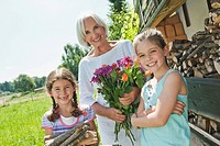 Germany, Bavaria, Granddaughters and grandmother in garden, smiling, portrait