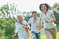 Germany, Bavaria, Man and woman running at picnic, smiling