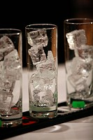Three coctail glasses with ice cubes