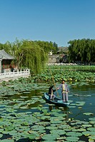 Two men in an old boat in a lily pond in Beihai Park in Beijing, China