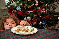 Young boy peers over a table to sneak a Christmas cookie from a plate with a Christmas tree in the background