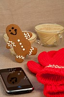 Close up of a happy gingerbread man dancing next to a glass of egg nog, an iPhone, red and white knit mittens