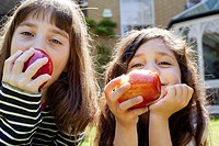 Girls eating apples outdoors