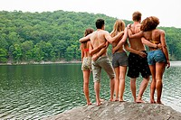 Friends standing together on rock at lakeside