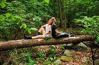 Couple leaning against each other on log in forest