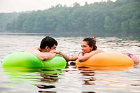 Young couple on inflatable rings on lake