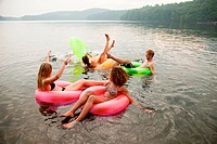 Friends playing in inflatable rings on lake