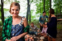 Young woman holding food cooked on campfire in forest