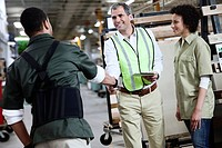 Two manual workers shaking hands in warehouse