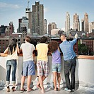 Friends looking at city skyline from rooftop