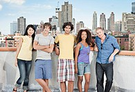 Portrait of group of friends on rooftop with skyline behind