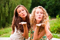 Two teenage girls fooling around in the countryside and blowing kisses