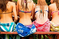 View of the backs of teenage girls sitting on a picnic table in bikinis