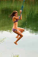 Girl swinging on a rope over a lake
