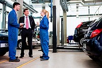Businessman with two car mechanics in repair garage