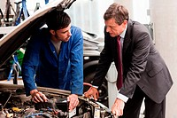 Businessman looking at car engine with mechanic