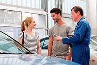 Mechanics talking to woman about car