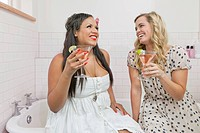 Women drinking martinis in bathroom