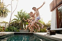 Young people jumping into swimming pool