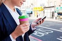 Close of businesswoman on street with coffee and smart phone