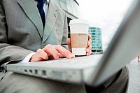 Close up of businessman with laptop and coffee outdoors