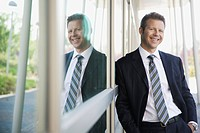 Smiling businessman leaning on glass wall