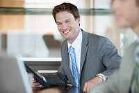 Portrait of smiling businessman at desk (thumbnail)