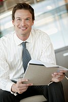 Portrait of smiling businessman with documents